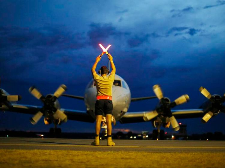 A ground controller guides a Royal Australian Air Force AP-3C Orion to rest upon its return to RAAF Base Pearce from a search for Malaysian Airlines flight MH370 over the Indian Ocean