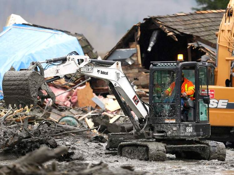 Workers dig through debris using heavy equipment in the mudslide near Oso