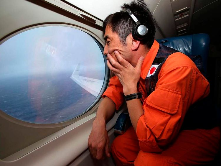 Crew member Koji Kubota of the Japan Coast Guard looks out an observation window aboard the Japan Coast Guard Gulfstream V aircraft as it flies over the southern Indian Ocean looking for debris from missing Malaysian Airlines flight MH370
