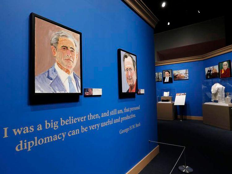 A self-portrait by former US President George W Bush hangs alongside a portrait of his father