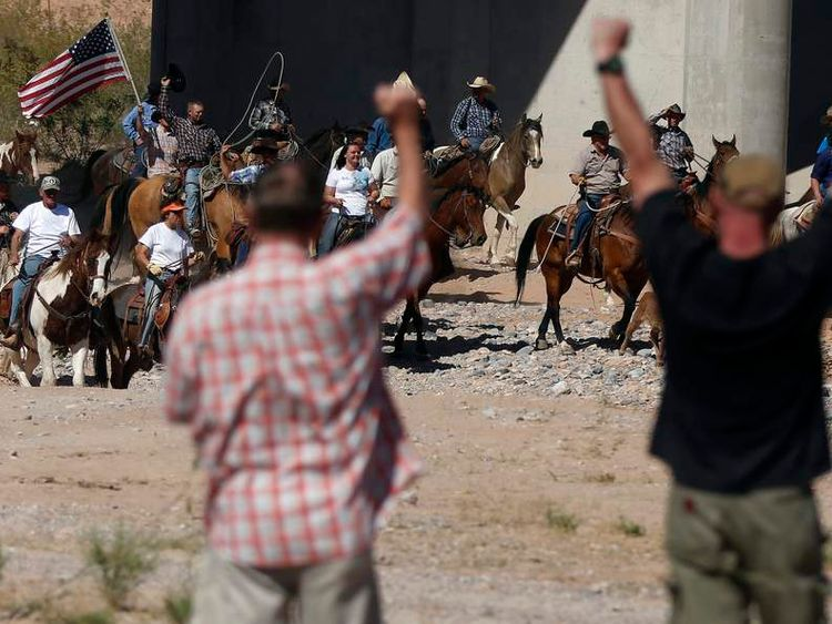 Protesters cheer on horseback riders as they herd cattle that belongs to rancher Cliven Bundy after they were released near Bunkerville