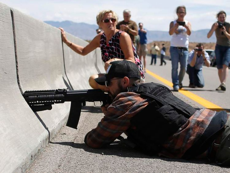 A protester aims his weapon from a bridge next to the Bureau of Land Management's base camp where seized cattle, that belonged to rancher Cliven Bundy, are being held at near Bunkerville