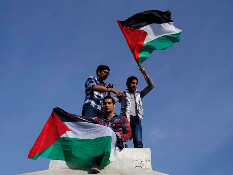 Palestinians hold national flags as they celebrate after an announcement of a reconciliation agreement in Gaza City