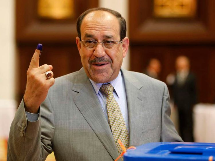 Nuri al-Maliki shows his ink marked finger as he votes during parliamentary election in Baghdad