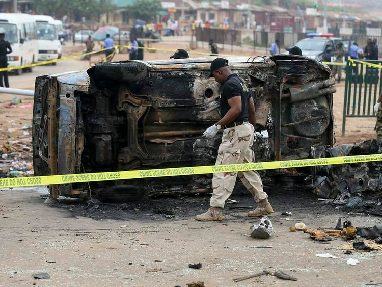 Ordnance experts examine an overturned vehicle at the site of a car bomb attack in Nyanya, Abuja
