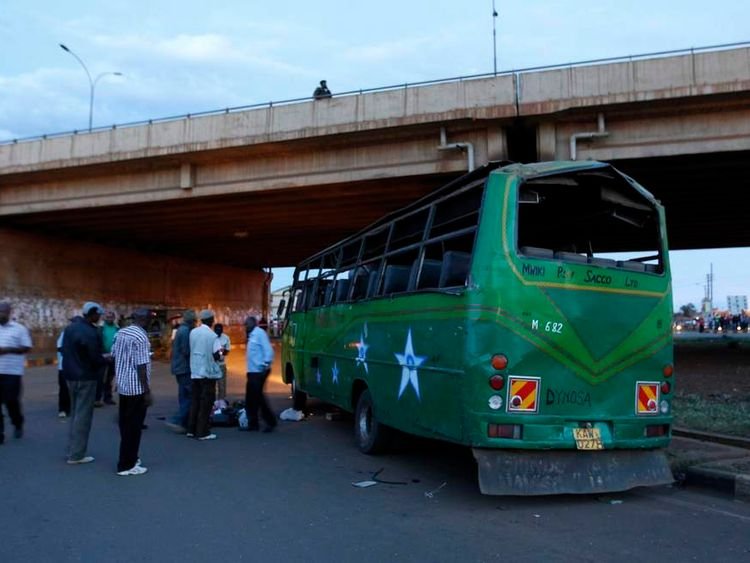 Bomb experts and plain clothes policemen gather at the scene of a bus explosion along the Thika super-highway in Kenya's capital Nairobi
