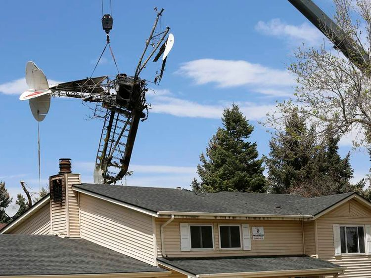 Wreckage of a small plane that crashed into a house is lifted by a crane in Northglenn