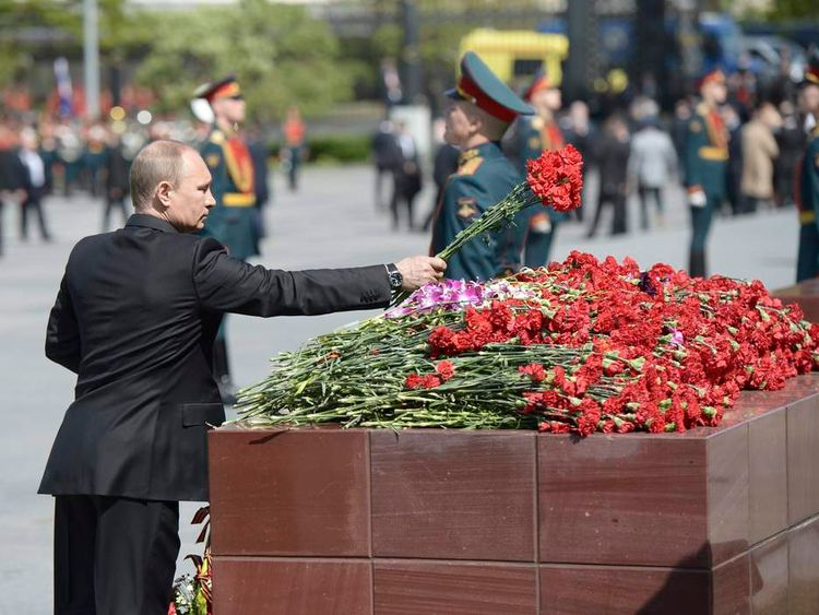 Russian President Putin lays some flowers during a wreath-laying ceremony at a memorial by the Kremlin wall on the eve of Victory Day celebrations in Moscow