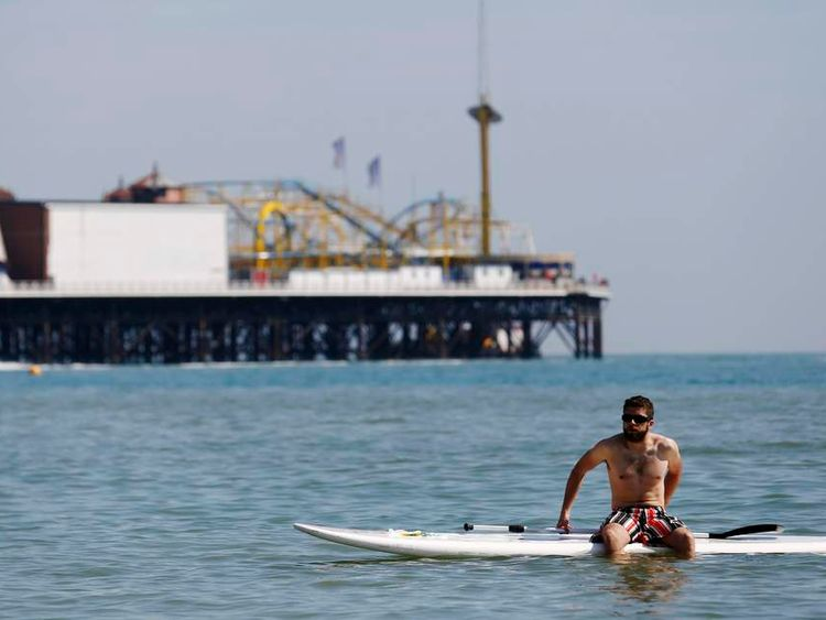 A paddleboarder rests on his board in the sunny weather on Brighton beach in southern England