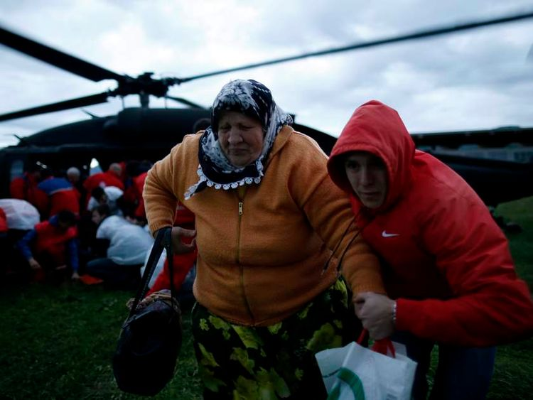 A woman and her son move away from the downwash of an European Union Force (EUFOR) helicopter after being rescued from the flooded Serici village.