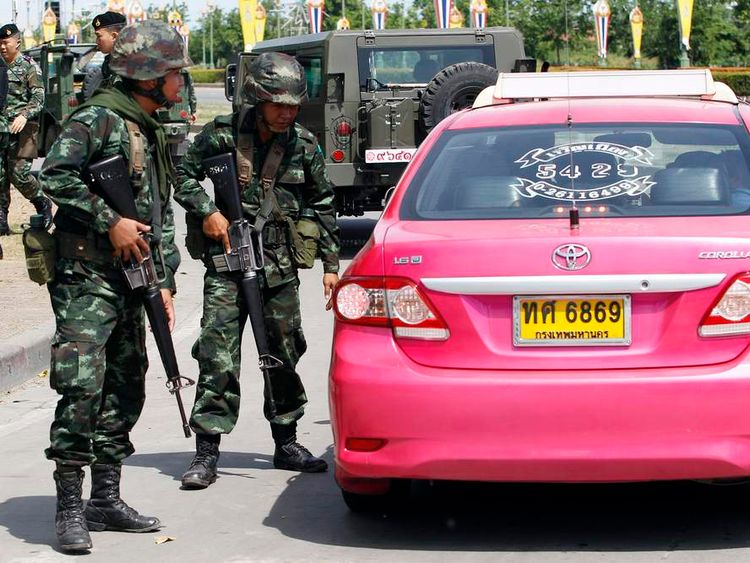 """Thai soldiers check a taxi near the site where pro-government """"red shirt"""" supporters gather, in the suburbs of Bangkok"""