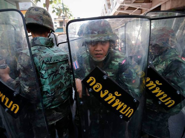 Soldiers use their shields while they change positions at Bangkok's shopping district