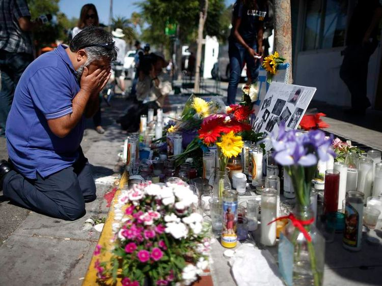 Jose Cardoso cries in front of a makeshift memorial for UCSB student Christopher Michael-Martinez in Isla Vista