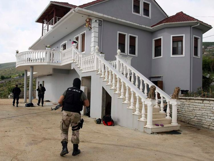 Members of the Albanian special police search a house in the village of Lazarat