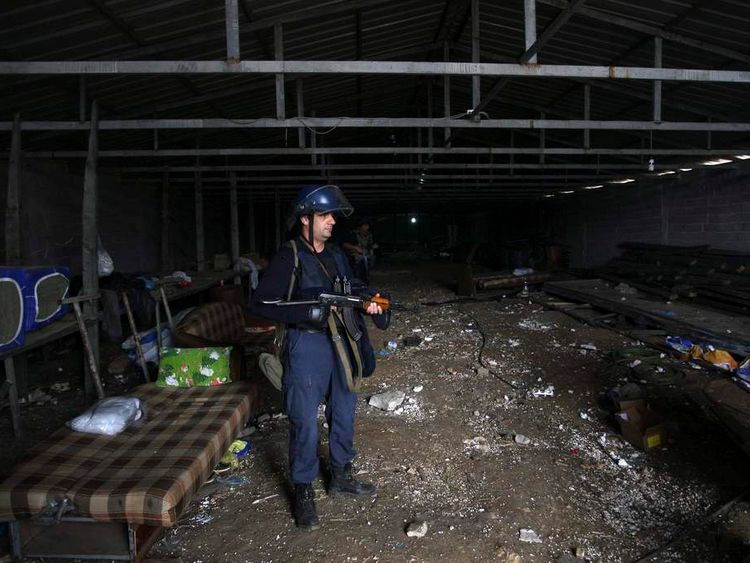 Members of the Albanian special police guard a depot that was used for cannabis trafficking in the village of Lazarat