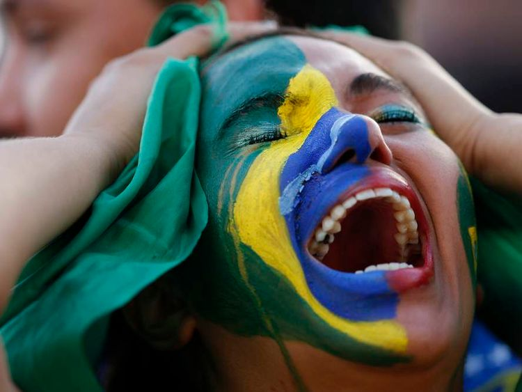 Fans of Brazil react while watching a broadcast of the 2014 World Cup semi-final against Germany at the Fan Fest in Brasilia