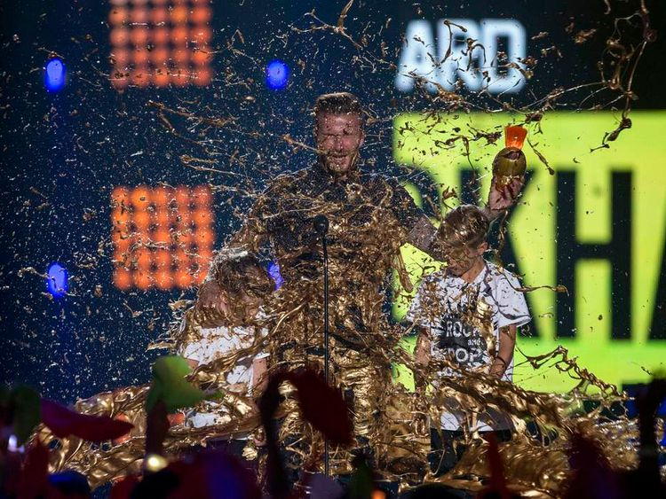 David Beckham accepts the Legend Award from sons during the inaugural 2014 Nickelodeon Kids' Choice Sports awards in Los Angeles