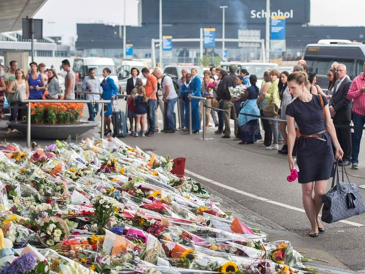 People look at a sea of flowers outside Schiphol Airport in memory of the victims of the crashed Malaysia Airlines flight MH17
