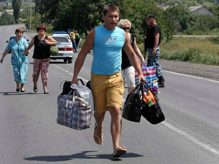Local residents carry their belongings as they flee from what they say was shelling by Ukrainian forces, in the town on the suburbs of Shakhtarsk