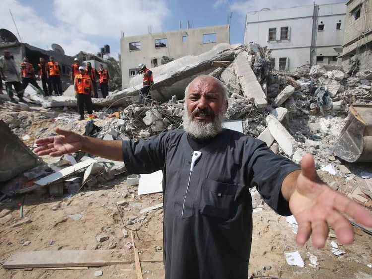 A Palestinian man reacts as rescue workers search for victims under the rubble of a house in Khan Younis in the southern Gaza Strip