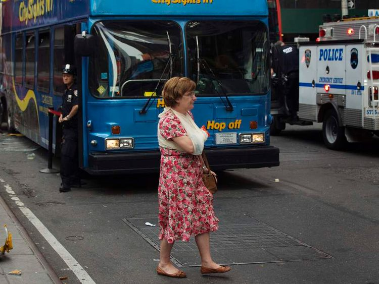 An injured woman walks away from the scene of a collision between two tour buses in the Times Square region of New York