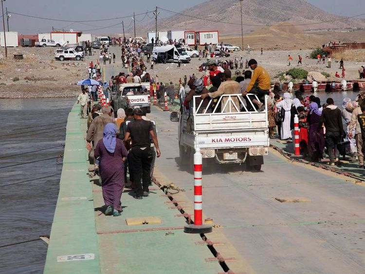 Displaced people from the minority Yazidi sect, fleeing the violence in the Iraqi town of Sinjar, re-enter Iraq from Syria at the Iraqi-Syrian border crossing in Fishkhabour, Dohuk Province