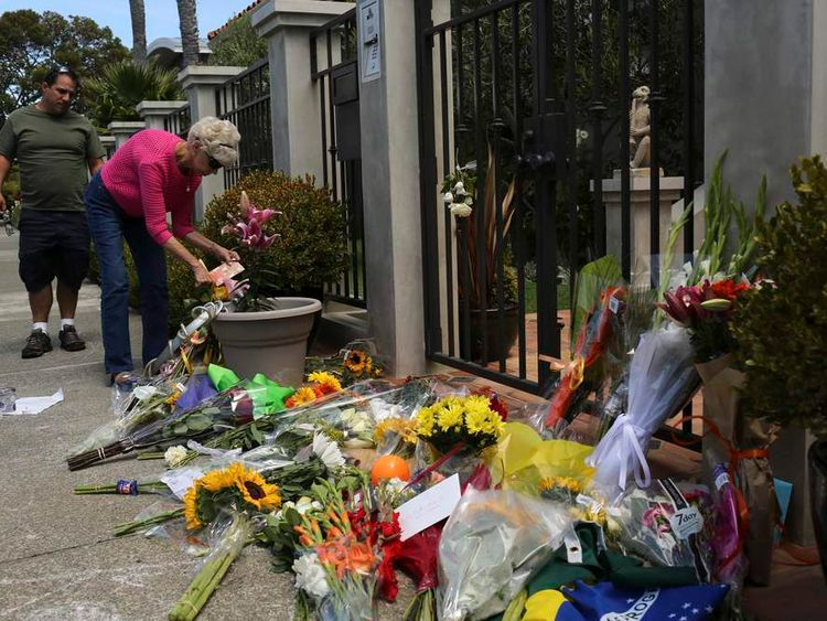 A woman places flowers and a card outside the home of actor Robin Williams in Tiburon, California