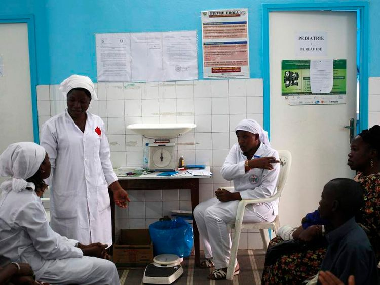 Nurses talk near a poster displaying a government message against Ebola, at a maternity hospital in Abidjan