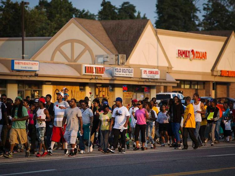 Demonstrators march down West Florissant during a peaceful march in reaction to the shooting of Michael Brown, near Ferguson, Missouri