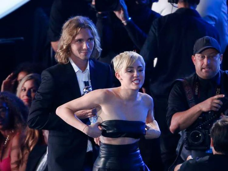 """Miley Cyrus leaves with her spokesperson Jesse after he accepted the award for video of the year for """"Wrecking Ball"""" during the 2014 MTV Video Music Awards in Inglewood."""