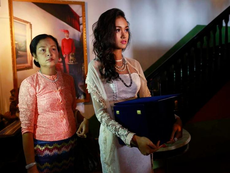 Myanmar's former beauty queen May Myat Noe holds box containing jewelled crown, before news conference in Yangon