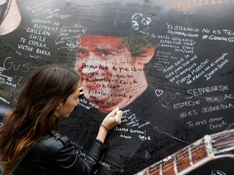 A woman writes a phrase on a picture of singer Cerati fixed on a wall in front of the clinic where Cerati died today in Buenos Aires
