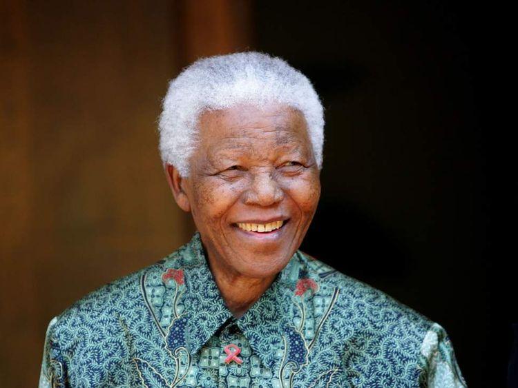 Former South African President Nelson Mandela smiles for photographers in Johannesburg