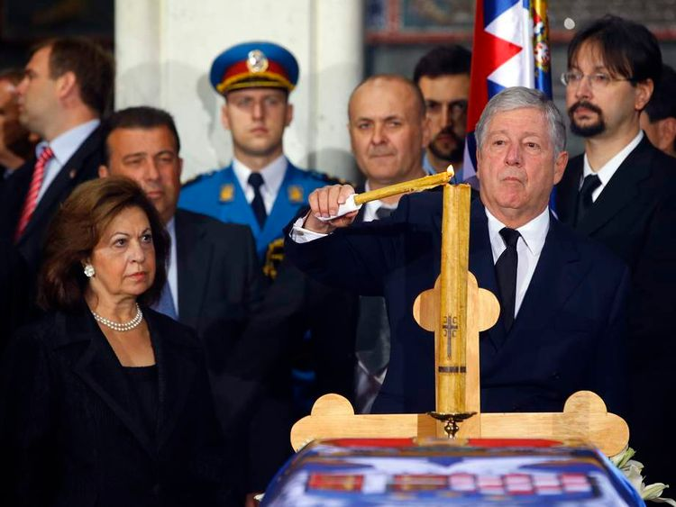 Serbian Crown Prince Karadjordjevic and his wife light a candle during the funeral of Serbian royals in Topola