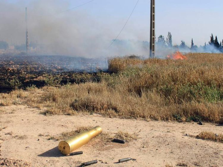 Empty ammunition casing and a fire are seen in a field after heavy fighting between Free Syrian Army fighters, and the forces of Syrian President al-Assad and Lebanon's Hezbollah at the al Barak area near Qusair town