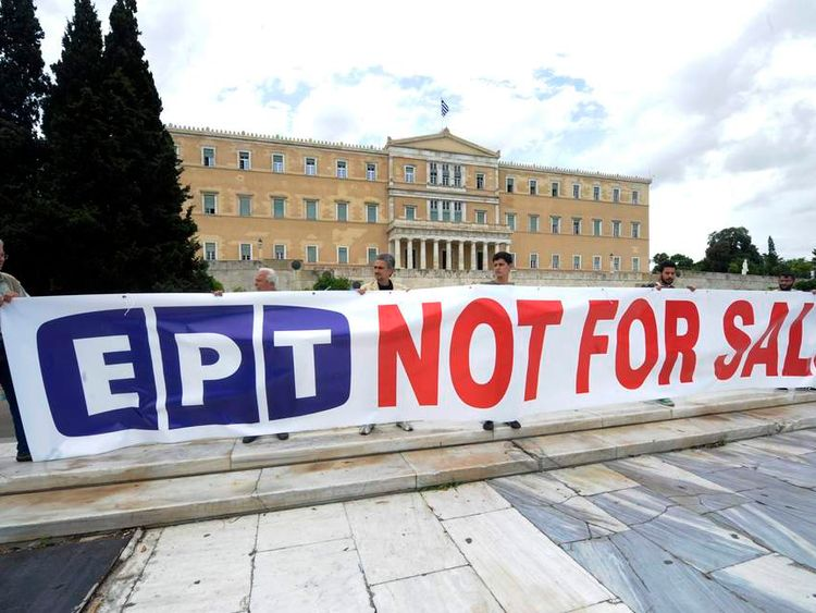 Protesters hold a banner in front of the parliament in Athens