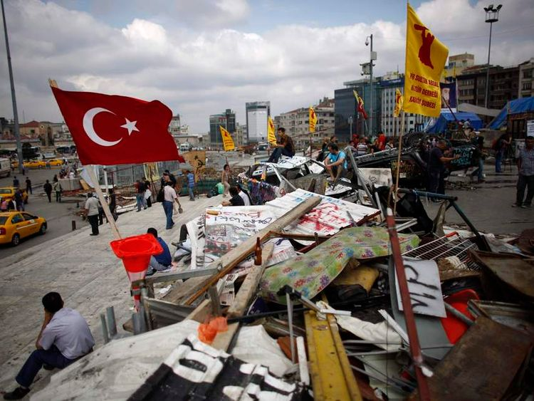 People sit and stand near the entrance of Gezi Park in central Istanbul