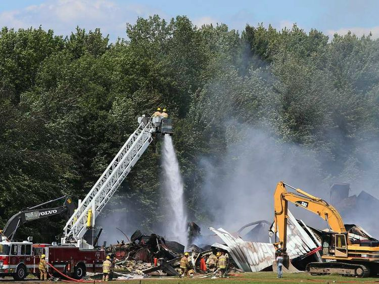 Firefighters work at the site of fireworks explosion