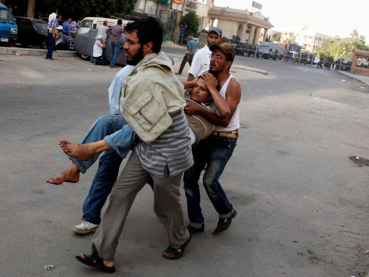 Protesters, who support former Egyptian President Mohamed Mursi, carry an injured man during clashes outside the Republican Guard building in Cairo