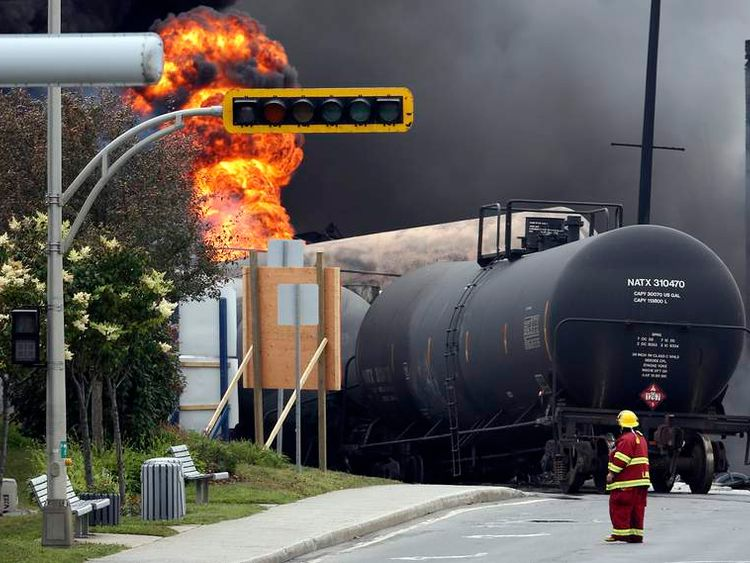 A firefighter walks past a burning train wagon at Lac Megantic