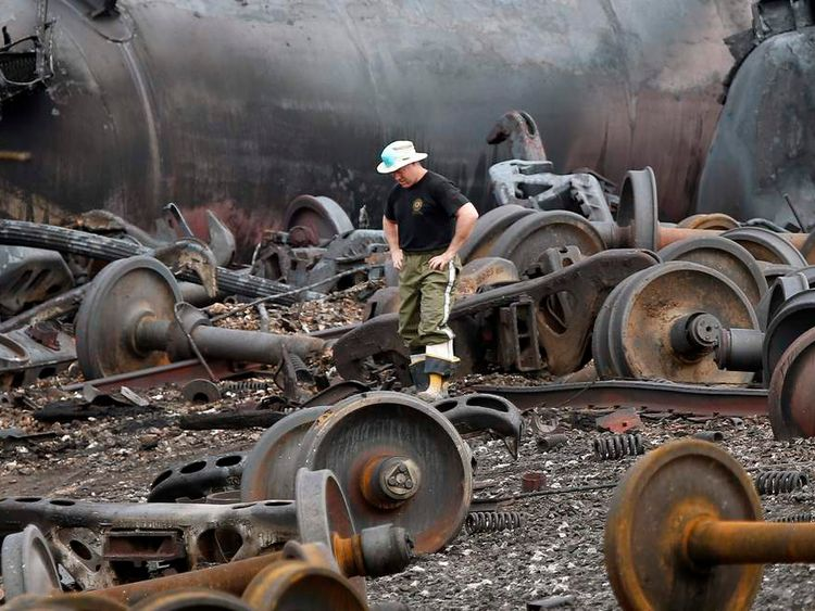 A police officer walks in front of a train wreck in Lac-Megantic