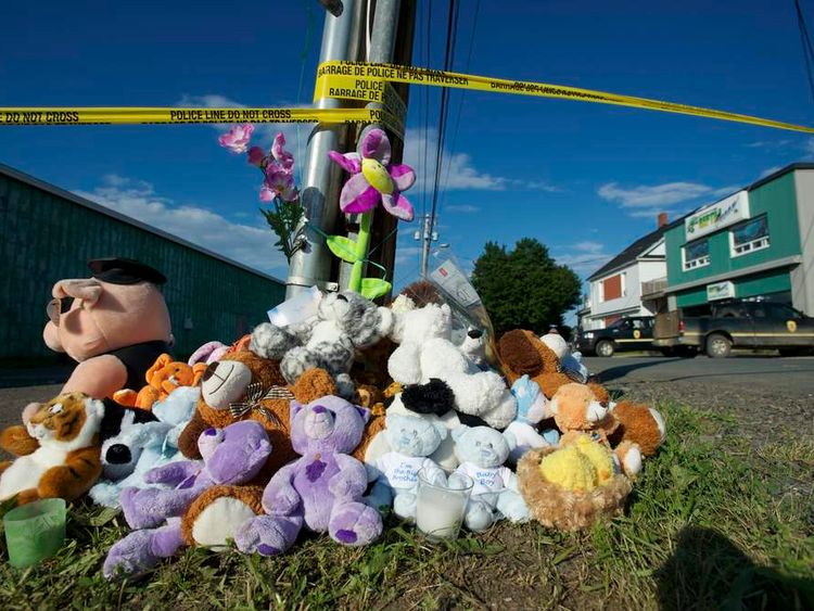 Stuffed animals are placed at a makeshift memorial across from the Reptile Ocean store on the evening of a vigil for Noah and Connor Barthe in Campbellton New Brunswick