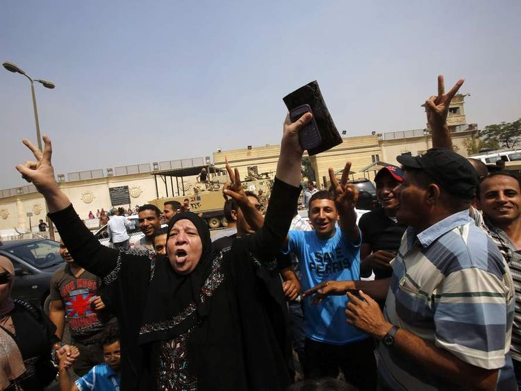 A supporter of Mubarak celebrates as she waits for his release in front of the main gate of Tora prison on the outskirts of Cairo