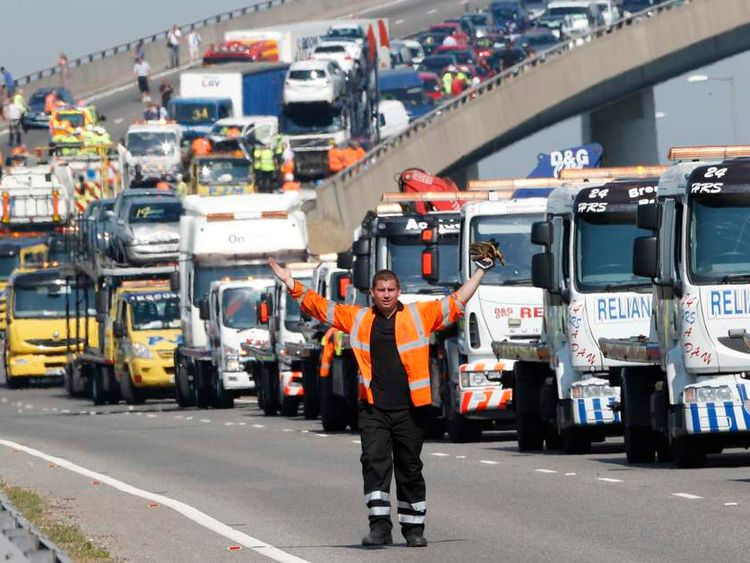 A rescue worker gestures in front of recovery trucks lined up to collect over 100 vehicles involved in multiple collisions, which took place in dense fog during the morning rush hour, on the Sheppey Bridge in Kent, east of London