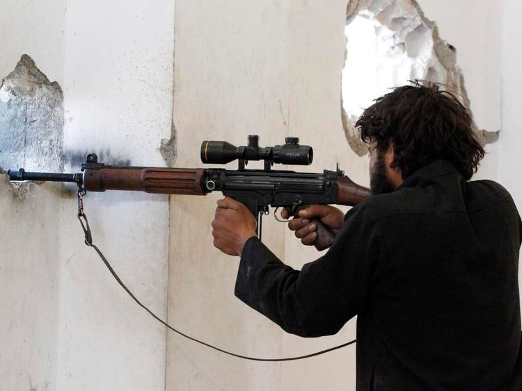 A Free Syrian Army fighter stands in a shooting position in Raqqa province, eastern Syria