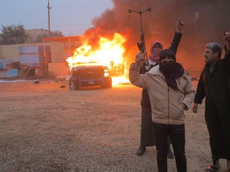 Protesters burn a police vehicle during fighting in Ramadi
