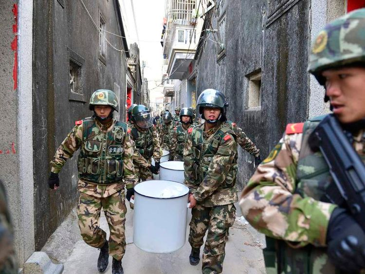 Paramilitary policemen carry crystal meth seized in a drugs raid away from Boshe village, China.