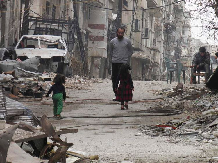 Civilians stand along a street filled with rubble and garbage in the besieged area of Homs