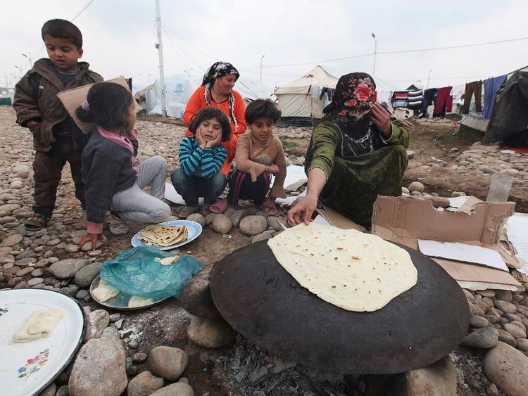 A Syrian refugee woman cooks bread outside a tent at Quru Gusik refugee camp on the outskirts of Arbil