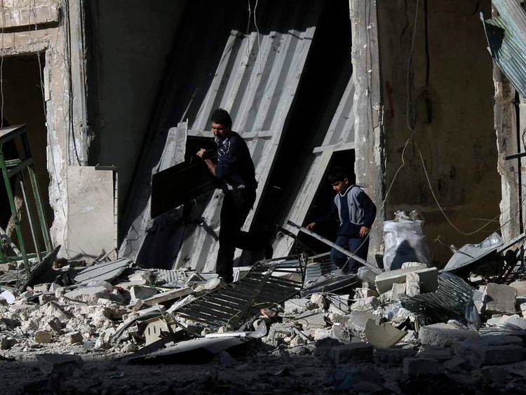 People collects objects from buildings damaged by what activists said was barrel bombs dropped by government forces in Aleppo's Dahret Awwad neighborhood